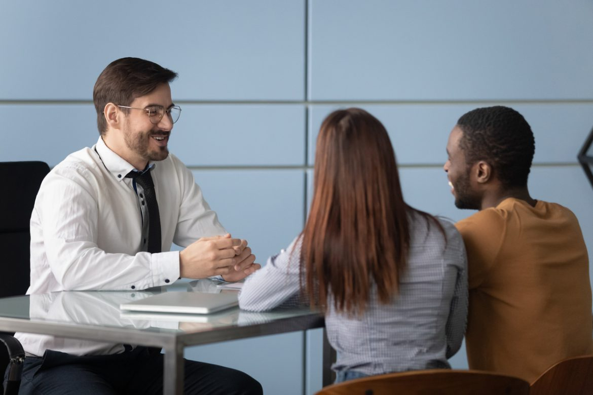 Multiracial clients meeting smiling bank worker at office